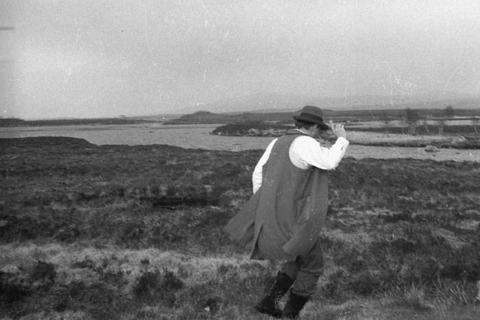 man met hoed loopt op voorgrond een drasland in, zwart-wit