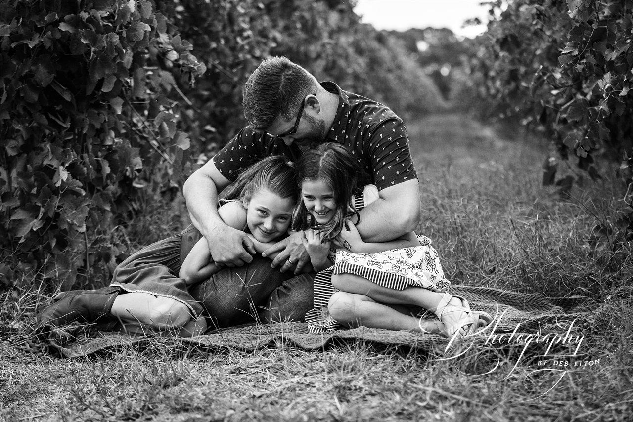 dad+cuddling+kids+onarug+vineyards+