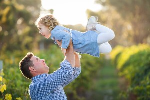 dad whizzing girl around laughing at their family portrait session by deb elton photography