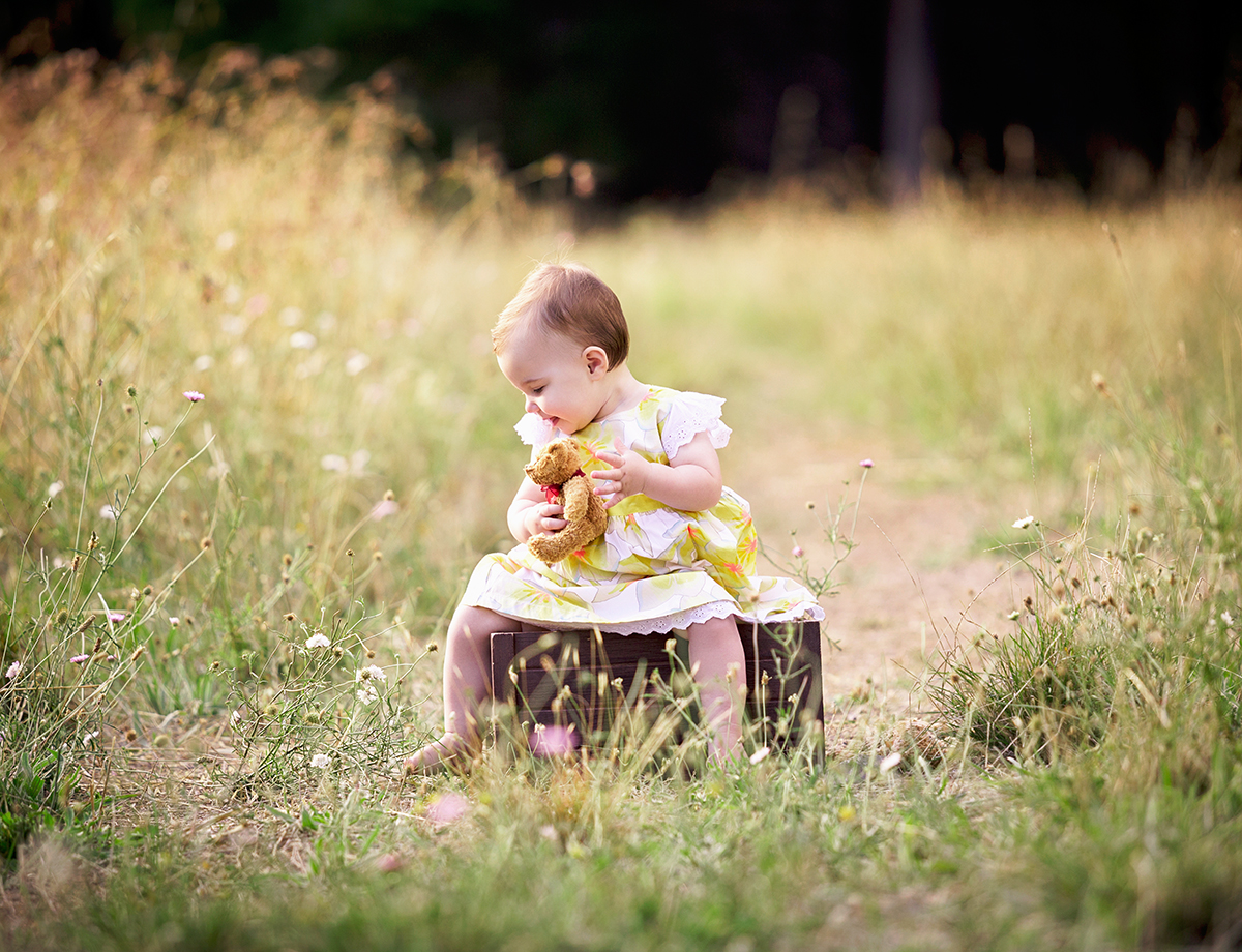 little baby girl with her teddy bear sitting in a field of flowers for her family portraits by deb elton photography