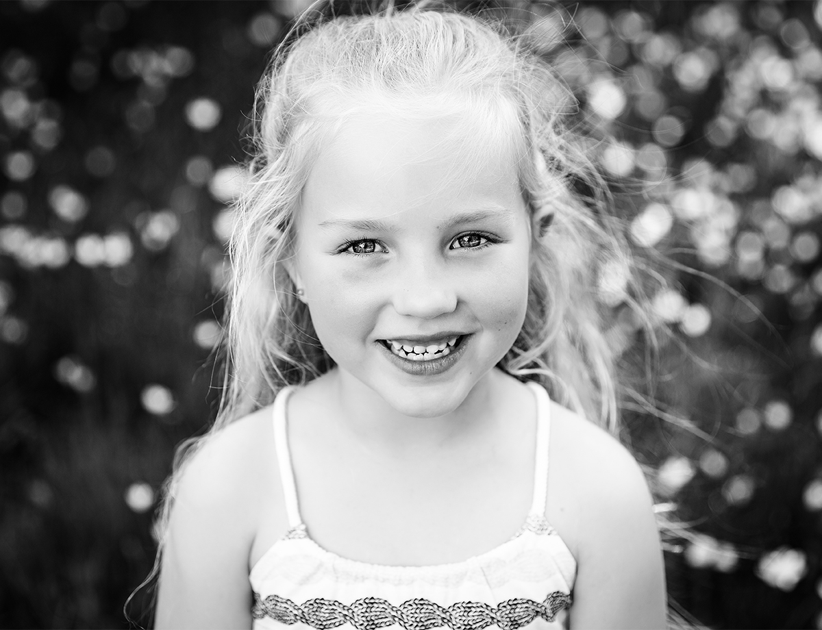 little girl smiling in spring surrounded by pretty light at their family photo session by deb elton photography