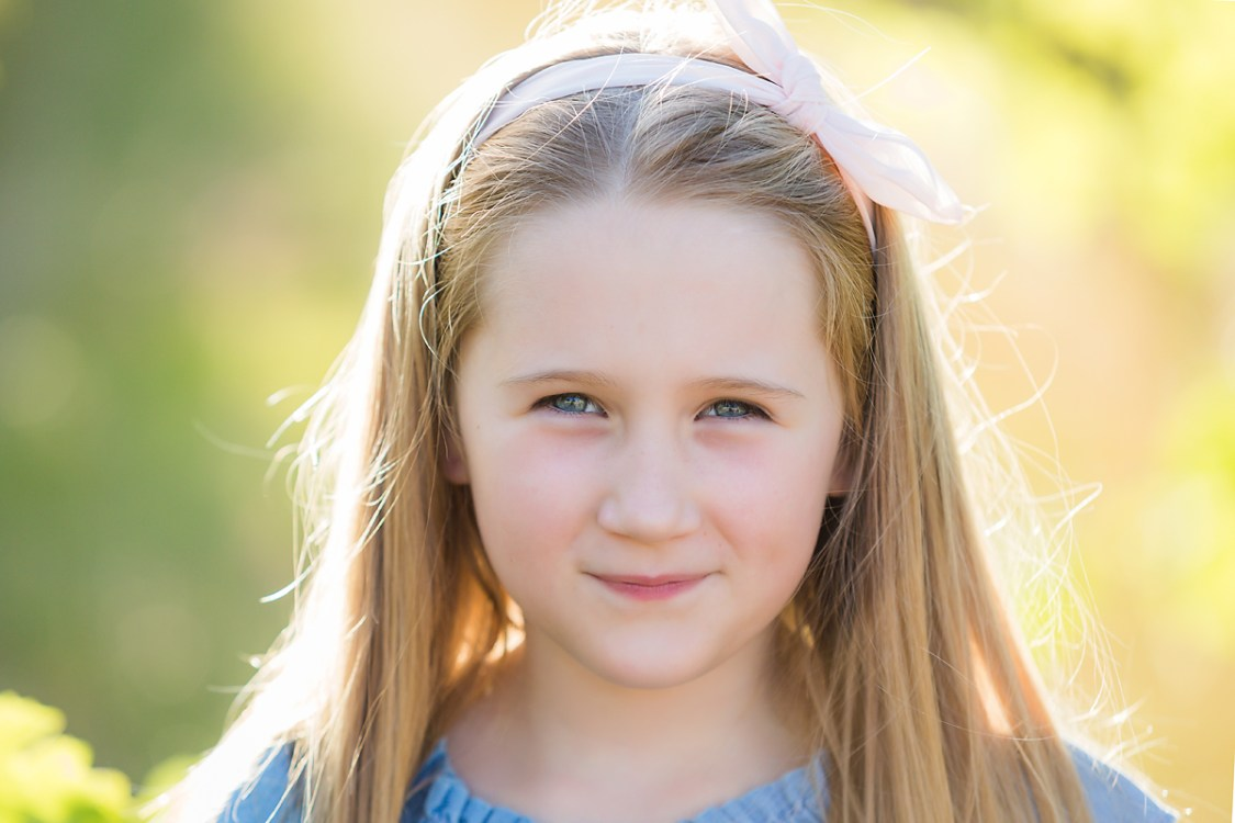 girl smiling and posing for family photos by deb elton photography