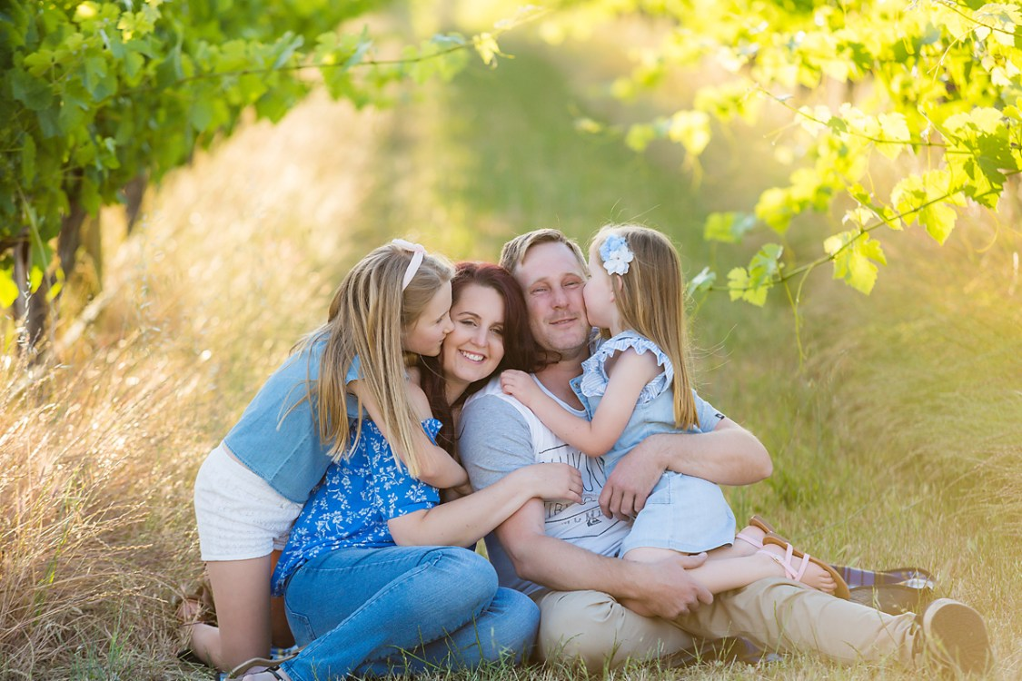 mum and dad and their  two children laughing and smiling on a rug in the vineyards at their family photo session by deb elton photography