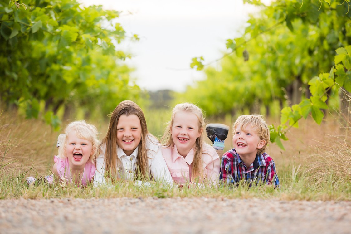 kids on their tummies smiling at their family photo session in the vineyards by deb elton photography