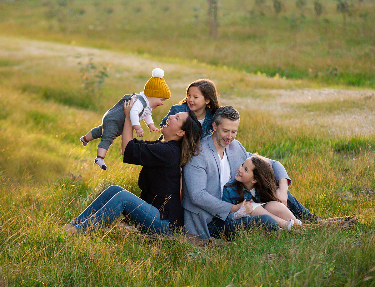 Family sitting on a rug in a field cuddling, laughing smiling happy at their family photo shoot by deb elton photogrraphy