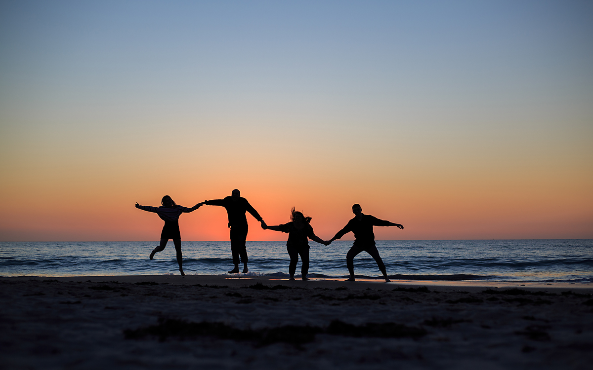 family in adalaide jumping on beach at sunset