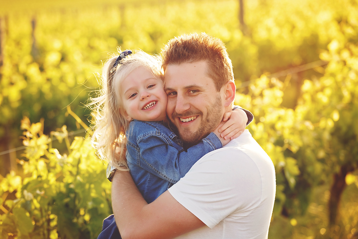 dad cuddling daughter in vineyards