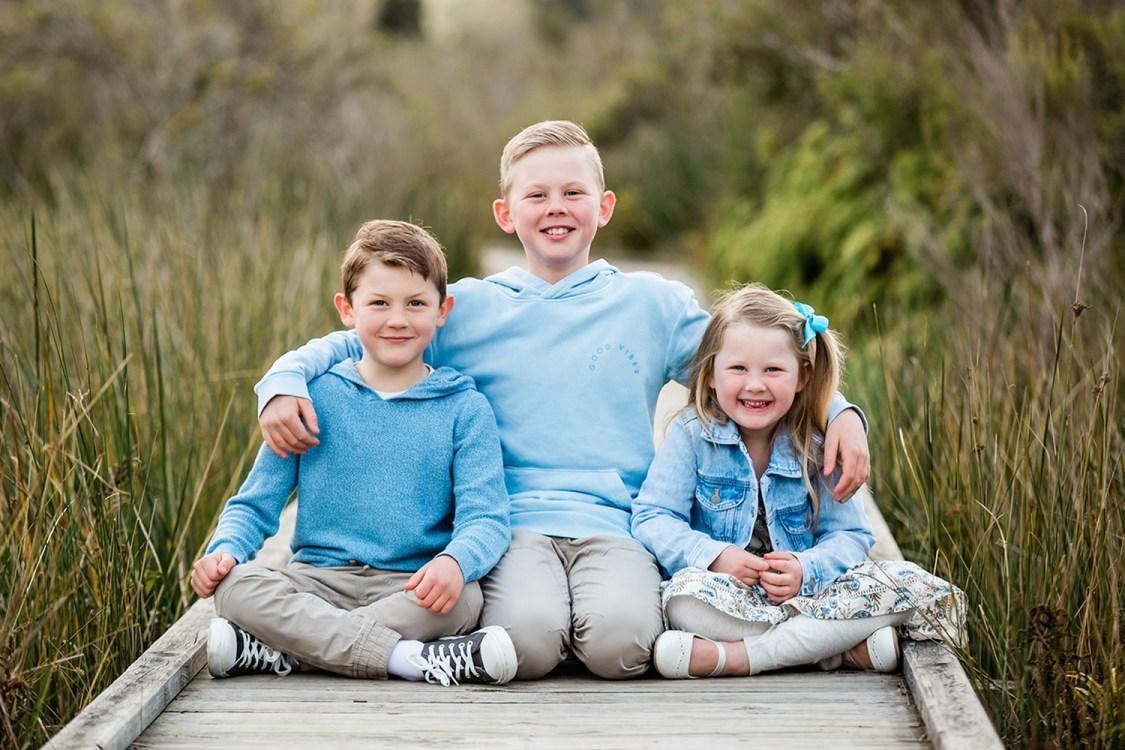 kids sitting on a boardwalk