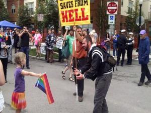 Una niña se enfrenta a un fanático religioso portando la bandera multicolor a favor de la igualdad de derechos