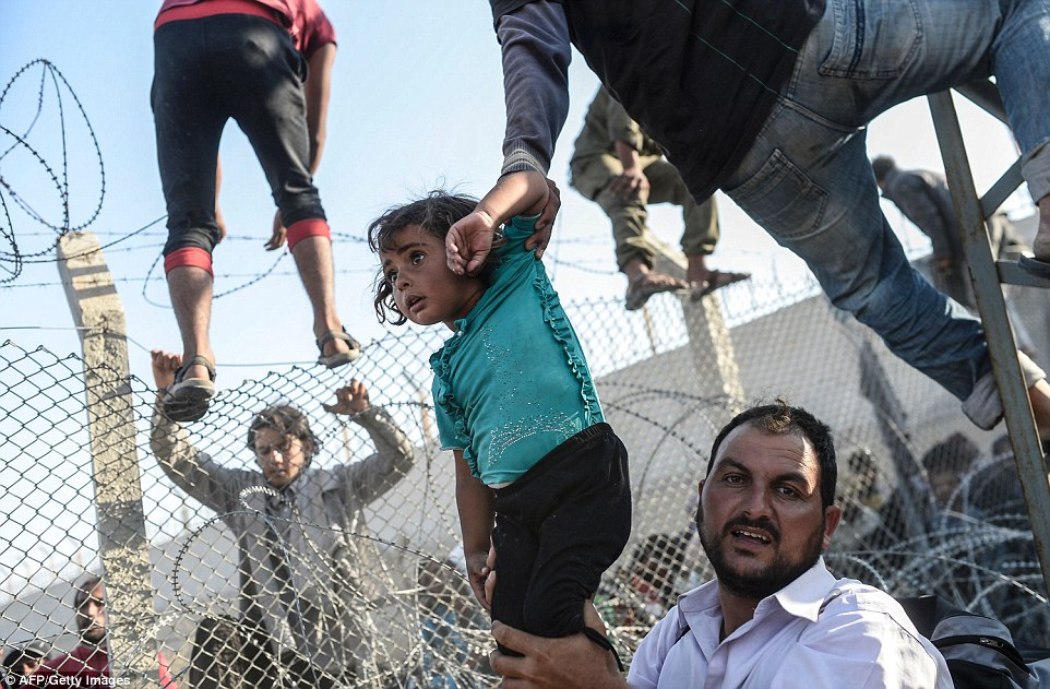 315708CF00000578-3452659-This_photo_shows_a_Syrian_child_fleeing_the_war_being_lifted_ove-a-1_1455813038303