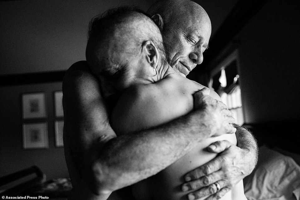 "In this image released by World Press Photo titled ""A Life in Death"" by photographer Nacy Borowick which won second prize Long Term Projects shows Howie and Laurel Borowick embrace in the bedroom of their home. In their 34- year marriage, they were diagnosed with stage-four cancer at the same time. New York, USA, March 8, 2013. A daughter photographs her own parents who were in parallel treatment for stage-four cancer, side by side. The project looks at love, life, and living, in the face of death. It honors their memory by focusing on their strength and love, both individually and together, and shares the story of their final chapters, within a year of each other. (Nancy Borowick, World Press Photo via AP)"