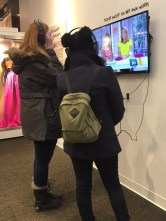 De Andrade and a friend listen to one of the multimedia presentations at the exhibit.