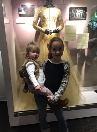 """Jadyn Foster and her sister Madeline, of Orlando, Fla., stand in front of Foster's favorite dress in the exhibit. """"I love Taylor so much. My dad took me here for my birthday today."""""""