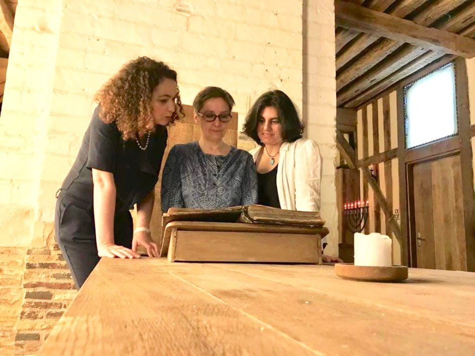 The three French women rabbis looking over an old copy of the talmud and pay homage to Rashi