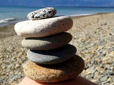 New Zealand beach, stacked rocks sitting balanced on a knee