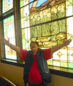 A Christian woman worshipping the Lord, hands in air, in front of a stained glass window.