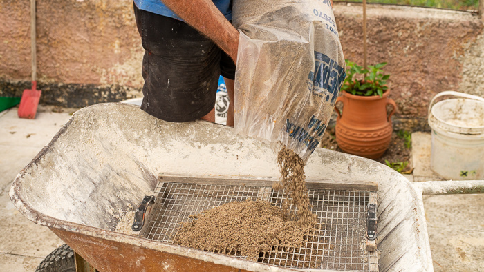 Building sand being poured onto a sieve on a wheel barrow.