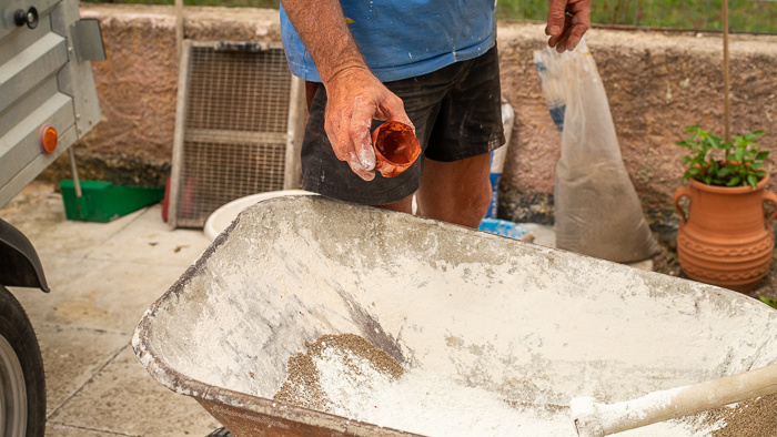 Concrete dye powder being added to a mix to make a concrete flower pot.