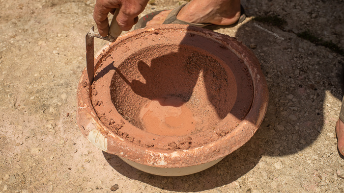 A trowel is being run around the outer edge of a mould holding a concrete flower pot to loosen the finished pot.
