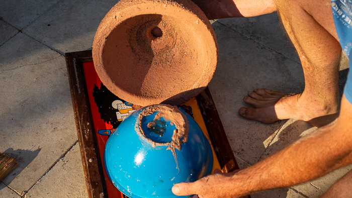 A homemade concrete flower pot is lifted carefully from it's inner mould