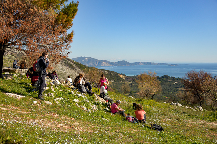 A group of hikers taking a breather on the side of a hill with the Zakynthos Marine Park in the distance. A beautiful blue sky.