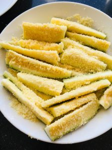 Courgettes bestrooid met strooikaas voor op de barbecue