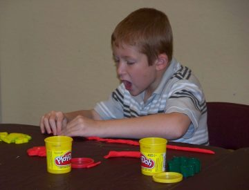 Sam creates with playdough