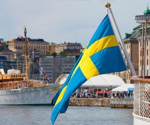 Sweden Stockholm - Swedish flag on one of the many boats anchored at The Old Town - Gamla Stan