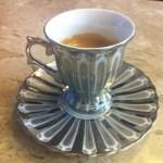 imagem de uma xícara de café de prata sobre uma mesa de marmore