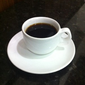 Imagem de uma xícara de café, sobre o pires. Numa mesa de marmore preta, em contraste com a xícara branca.