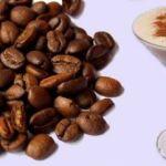 Imagem de um punhado de grãos de café torrado, sobre um fundo branco. Ao lado, à direita, uma taça de short drink com a bebida cremosa bege clara e canela salpicada.