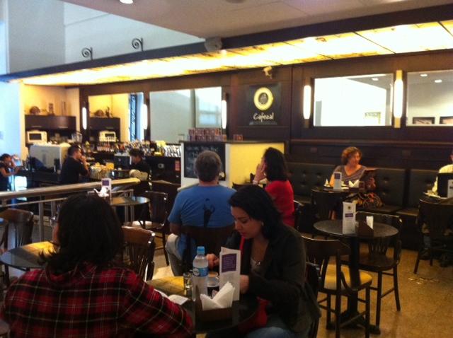 Imagem do salão de café, com várias mesas redondas e cadeiras. Há várias pessoas sentadas e pode-se ver o balcão ao fundo e espelhos nas paredes atrás do balcão e das mesas.