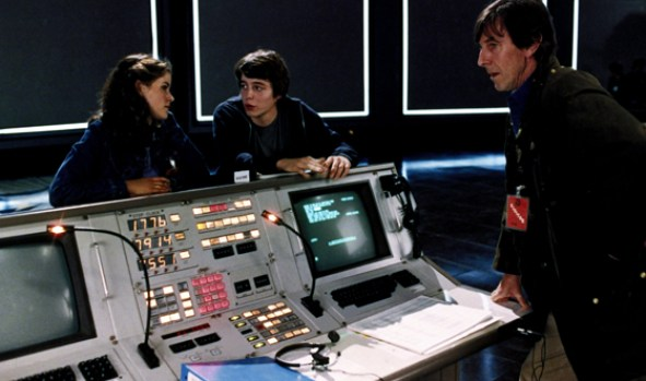 three people standing with old computer console