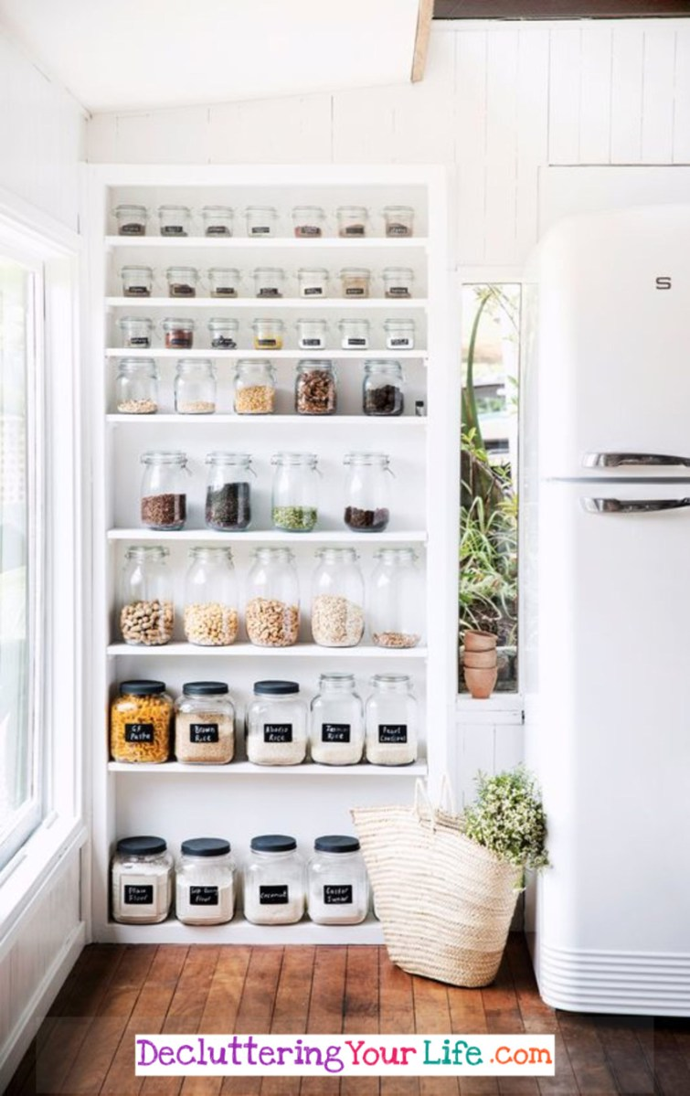 Declutter your kitchen!  This beautiful white kitchen uses this simple DIY shelves idea to organize and declutter in their kitchen.  LOVE all the different size canisters for displaying their pantry goods!