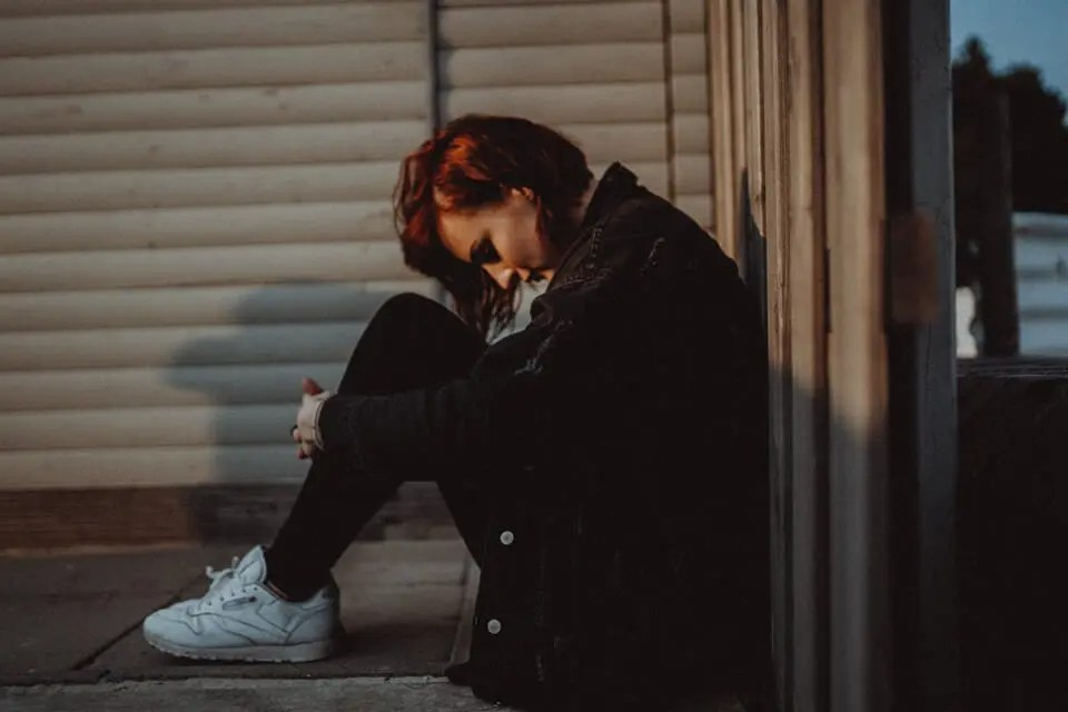Woman crouched down lost in negative thoughts