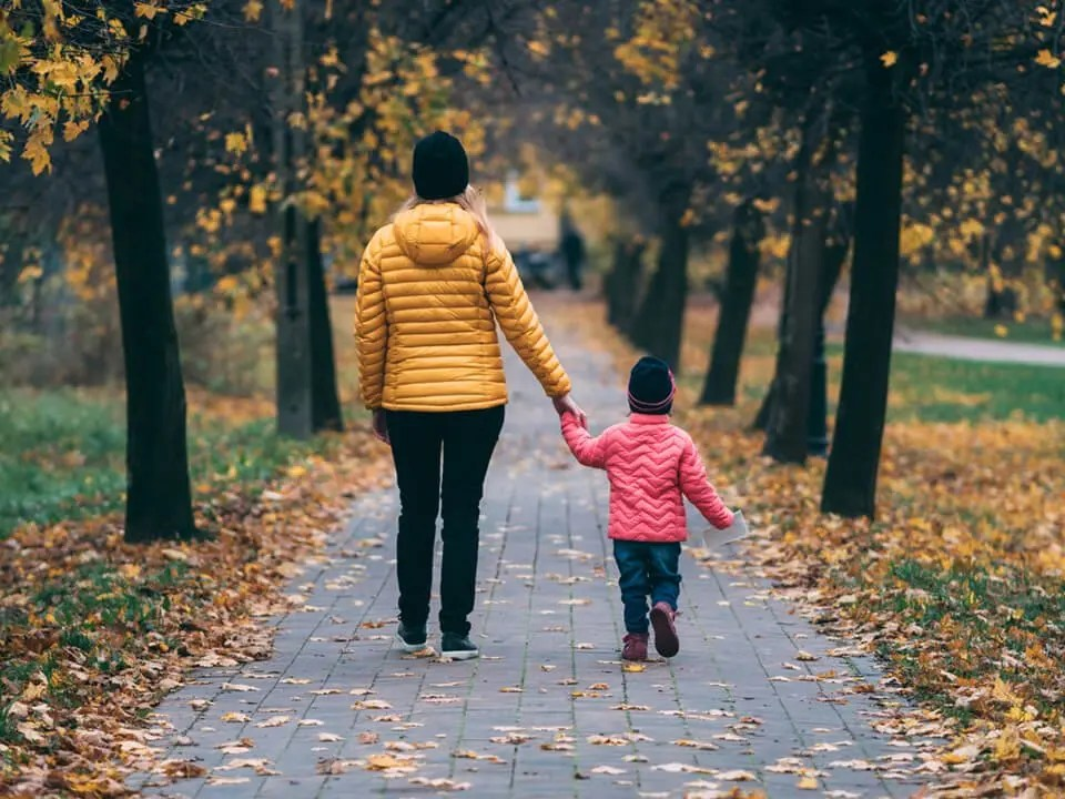 Woman walking outside with her daughter.