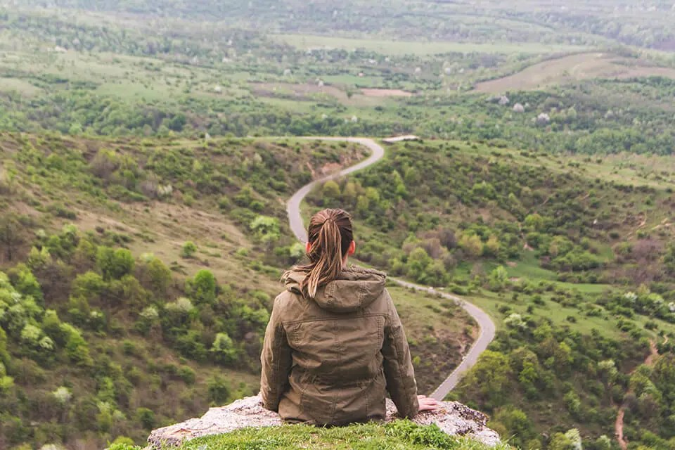 Woman sitting on hill, overlooking a long winding trail