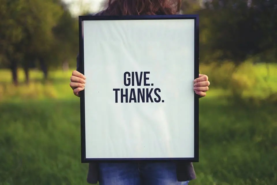 """Woman holding up portrait with the word """"Give thanks."""" on it."""