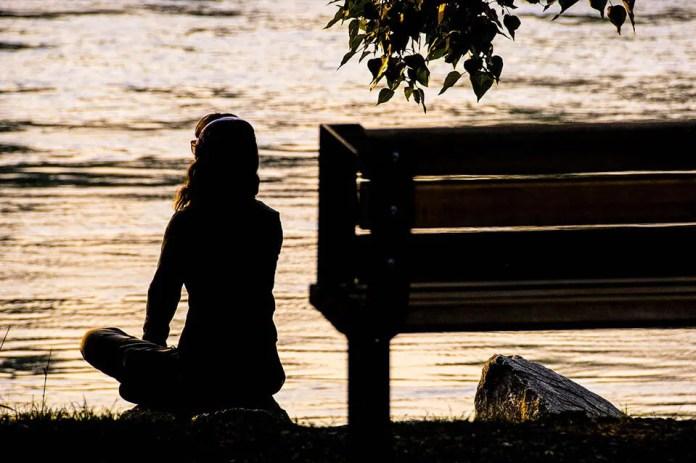 पार्क में बैठी महिला पानी के पास ध्यान लगा रही थी