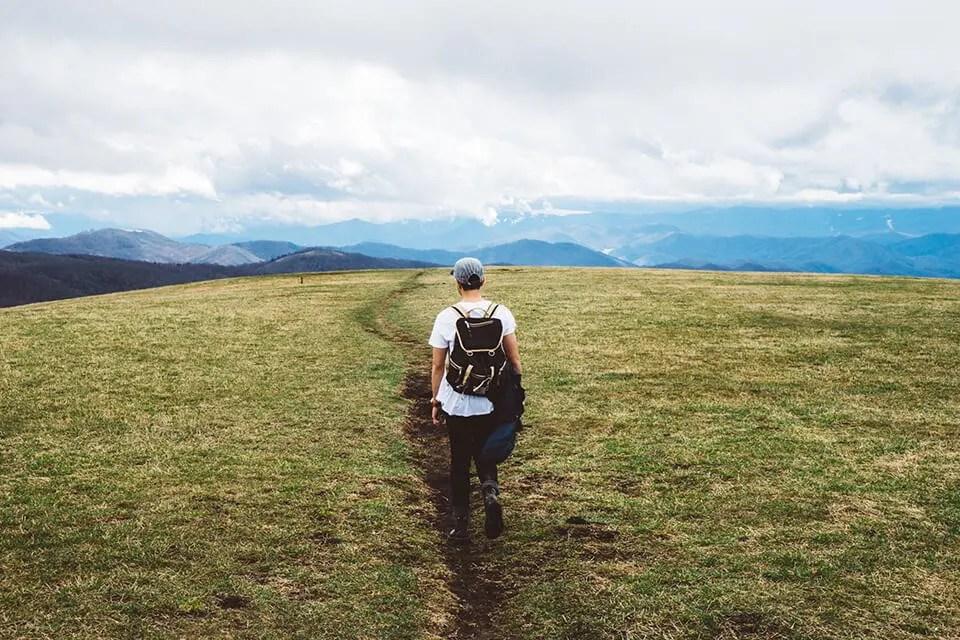 Man walking down a trail in a large open field