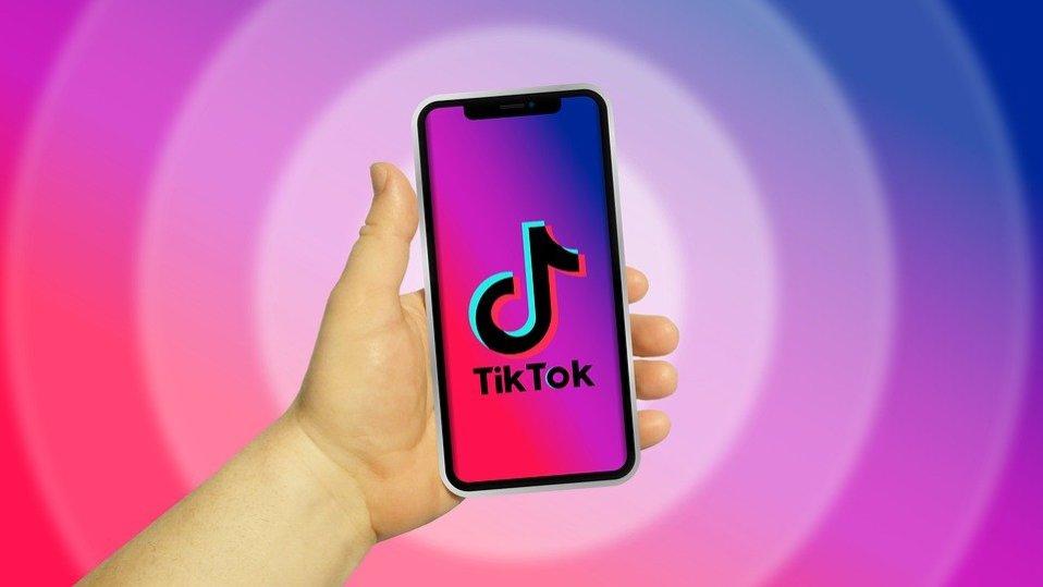 Main qui tient un téléphone avec TikTok en fond d'écran.