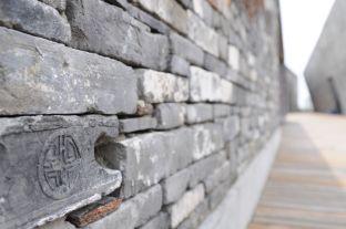 """Antiguo sello de una empresa que fabricó los materiales originales usados, tras un proceso de reciclaje, para construir la fachadas del museo Ningbo. """"No son escombros, es historia, tiempo y experiencias, mucha gente ha tocado estos ladrillos"""", dice el arquitecto Wang Shu."""