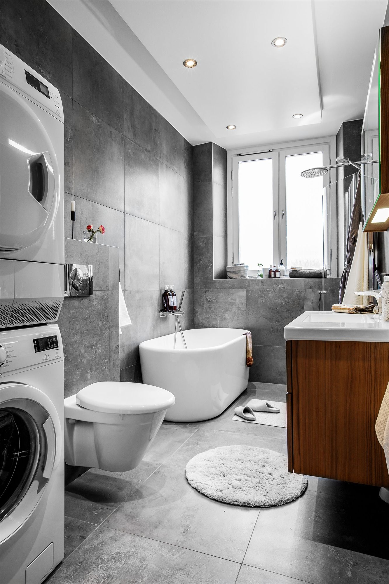 ванная комната ванна раковина комод подвесной унитаз стиральная сушильная машина окно серый керамогранит