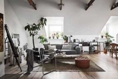 гостиная мансарда окно диван подушки столик стеллаж декор цветы комнатное дерево пуф ковер кресло