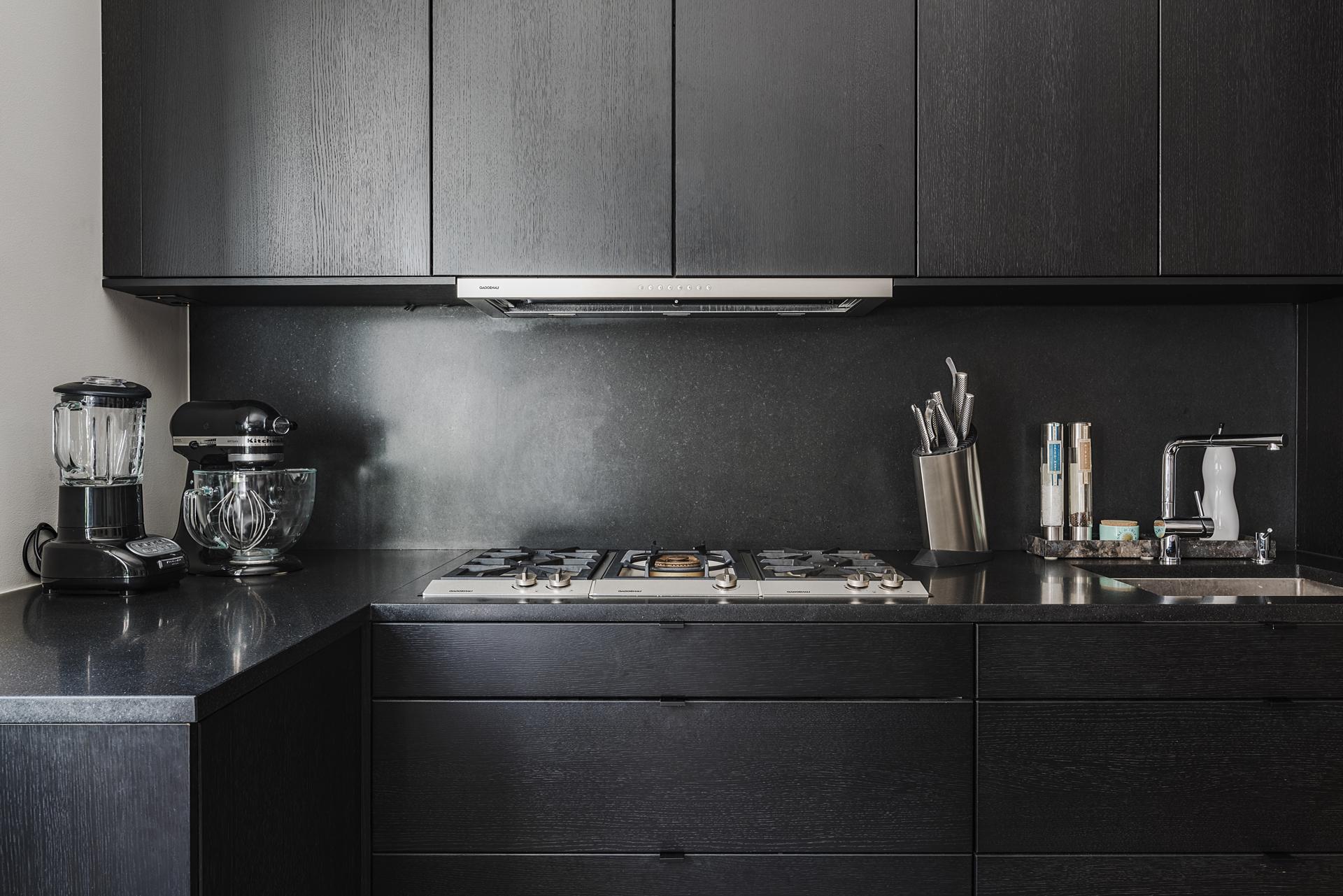 кухня темная мебель столешница плита встроенная вытяжка кухонная техника