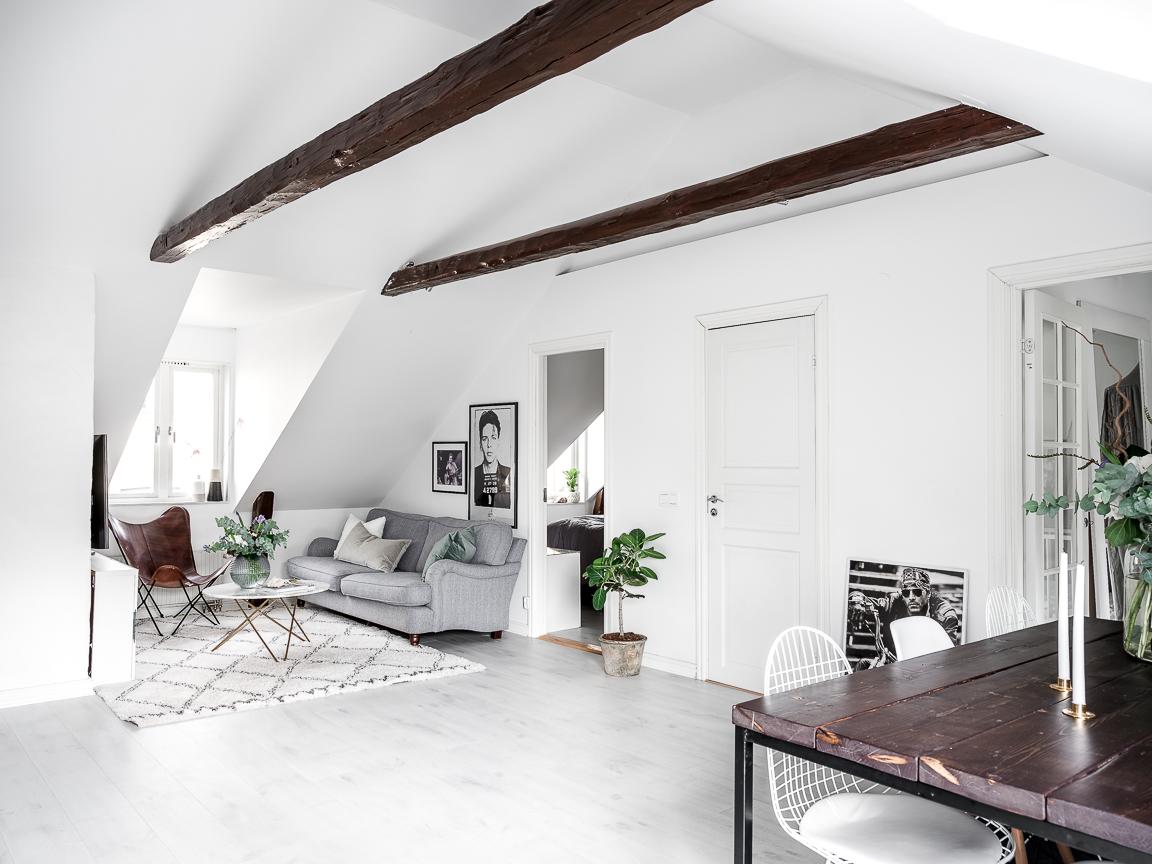 высокий потолок мансарда окно балки гостиная диван столик ковер