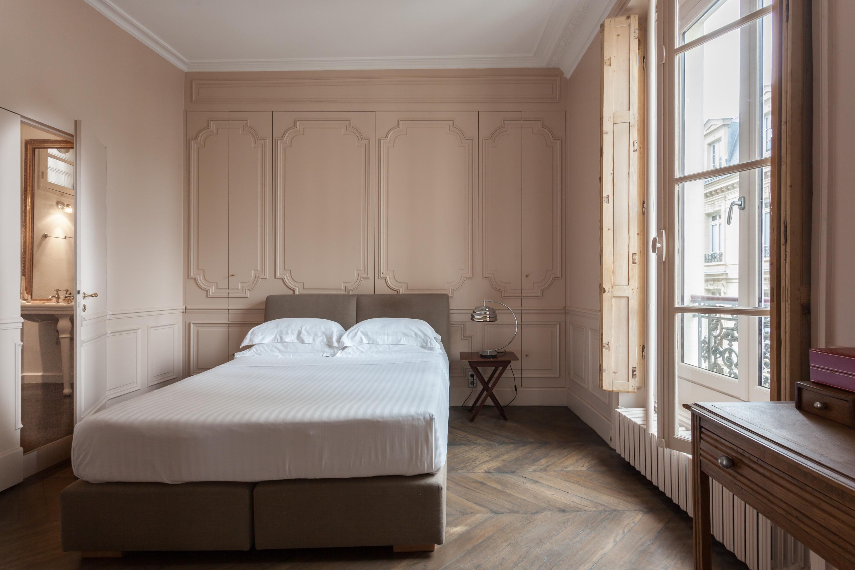 спальня бежевые стены молдинги паркет елочка деревянные ставни французские окна