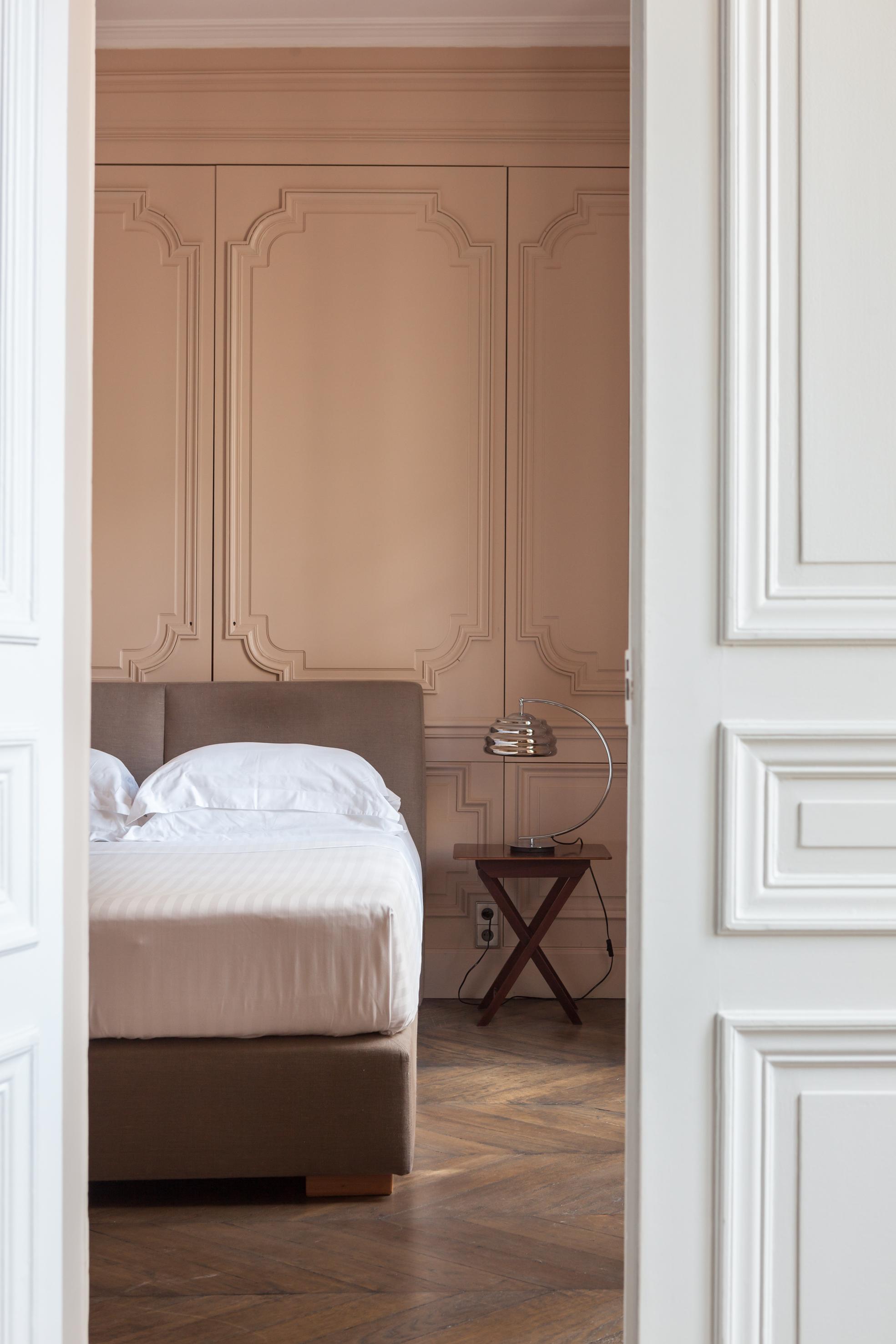 спальня кровать изголовье бежевые стены молдинги паркет белая дверь