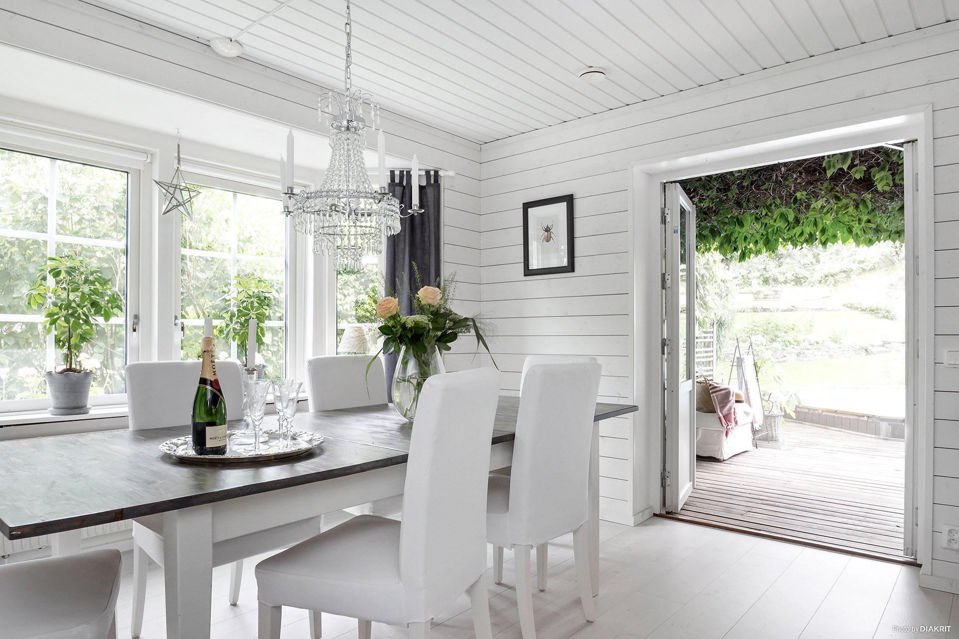 обеденный стол стулья белые стены хрустальная люстра выход на террасу