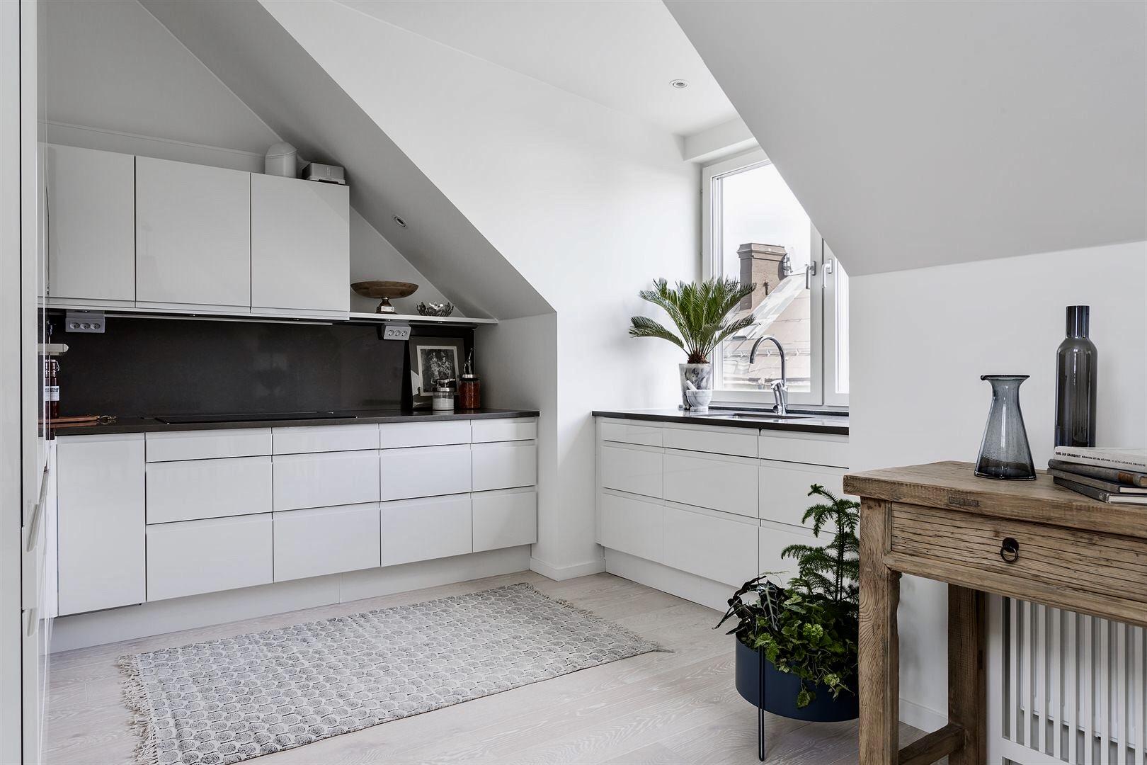 кухня белые гладкие фасады светлый пол белые стены мансарда черная столешница деревянная консоль окно